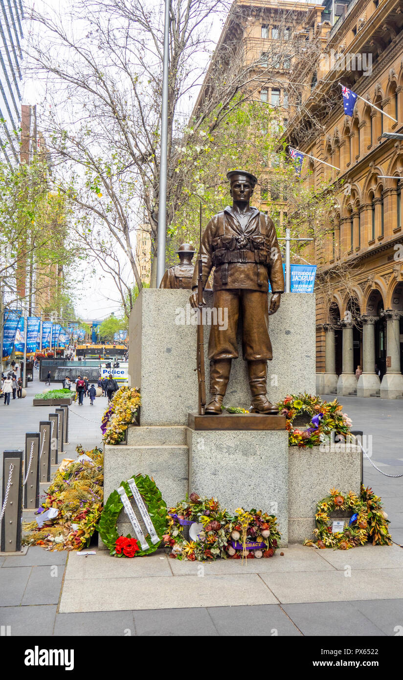 Wreathes placed at base of bronze statue of a sailor commemorating ANZAC day in Martin Place Sydney NSW Australia. - Stock Image
