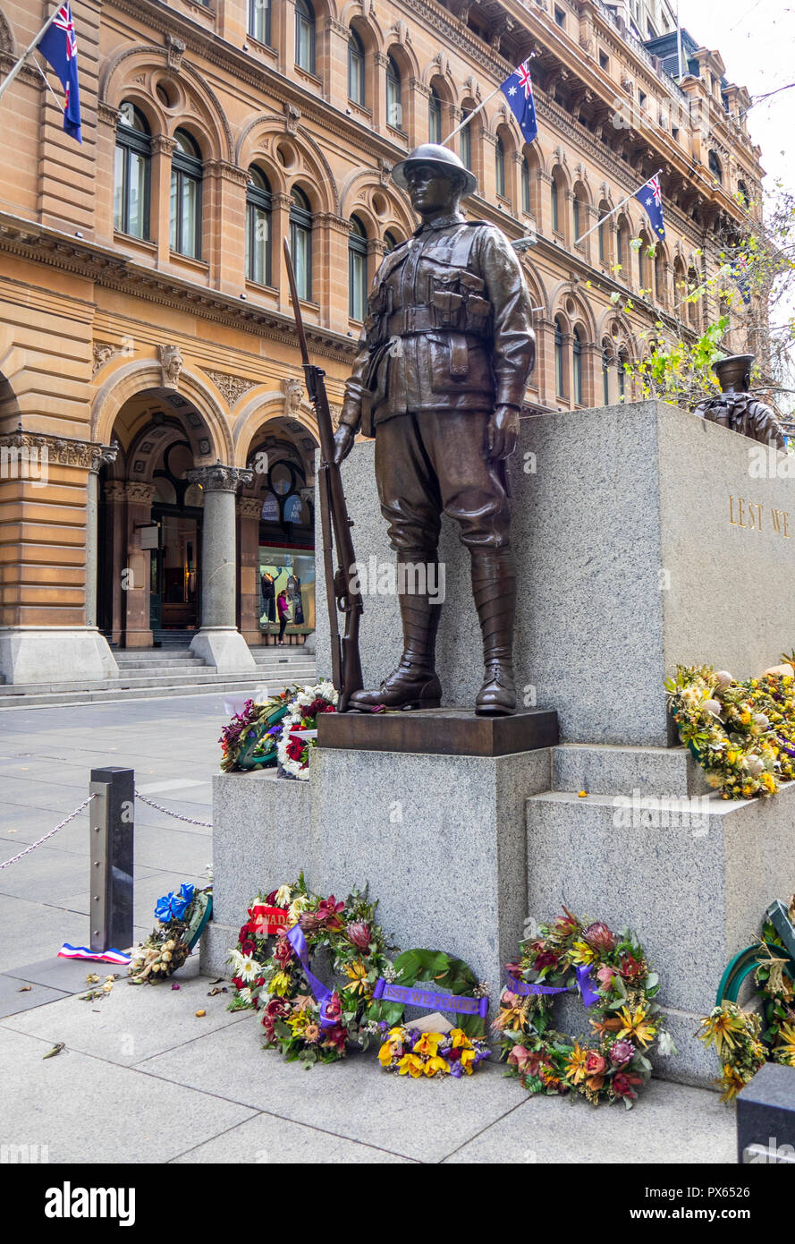 Wreathes placed at base of bronze statue of a soldier commemorating ANZAC day in Martin Place Sydney NSW Australia. - Stock Image