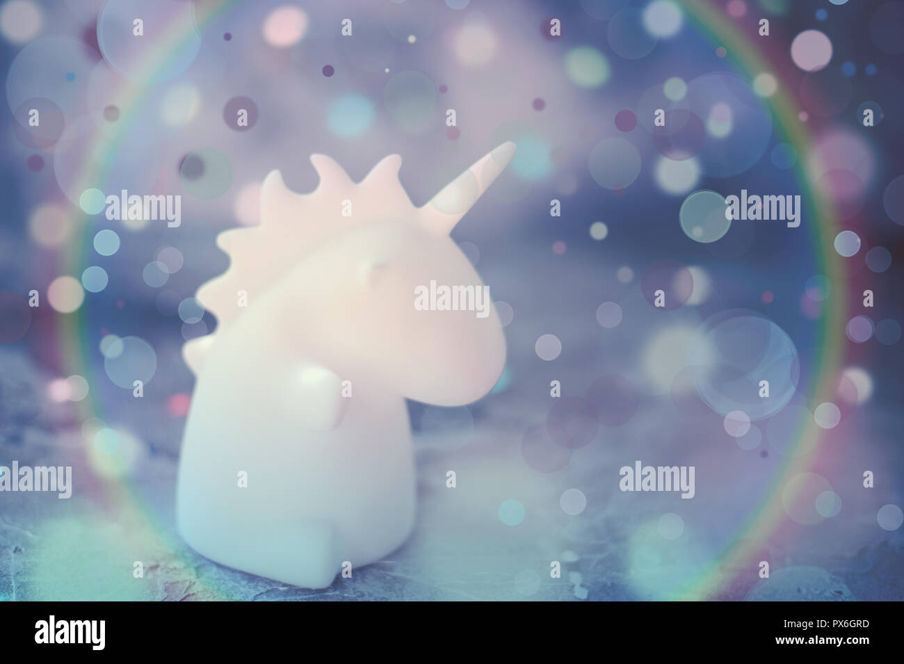 Unicorn shape table lamp illuminated - Stock Image