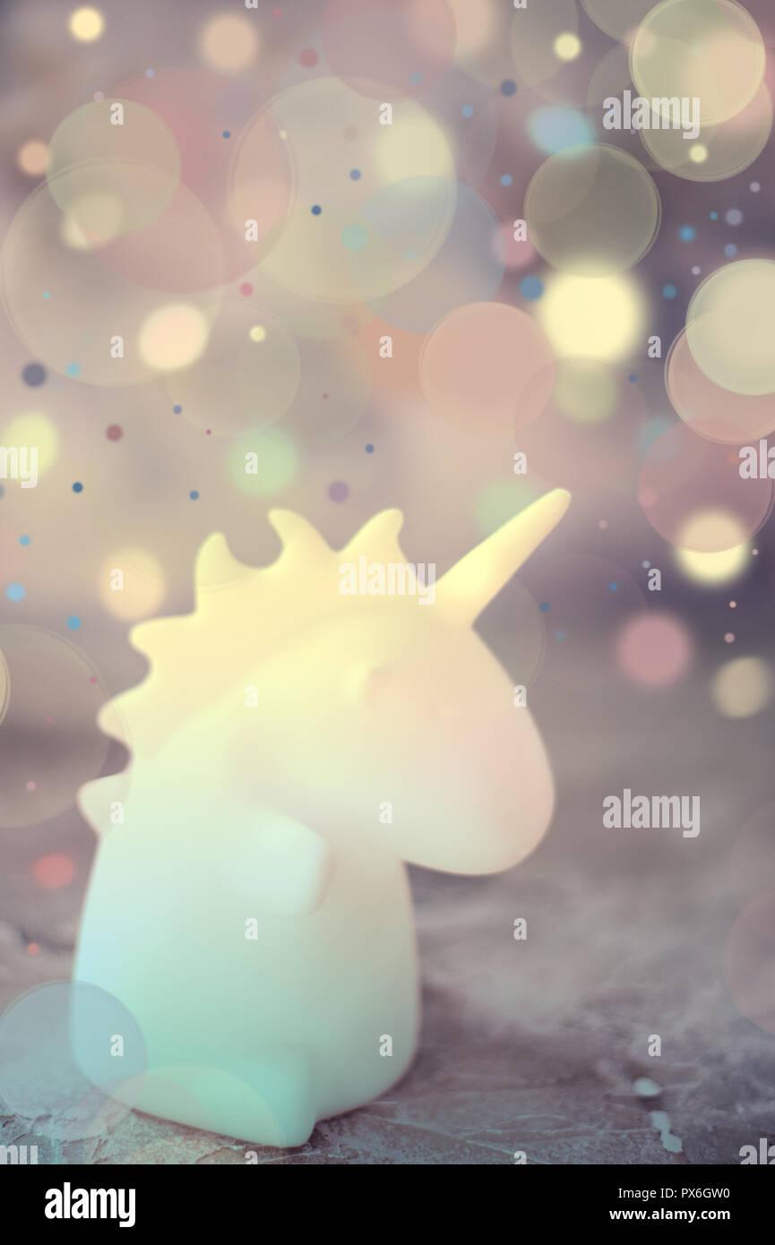 Unicorn shape table lamp illuminated - Stock Image