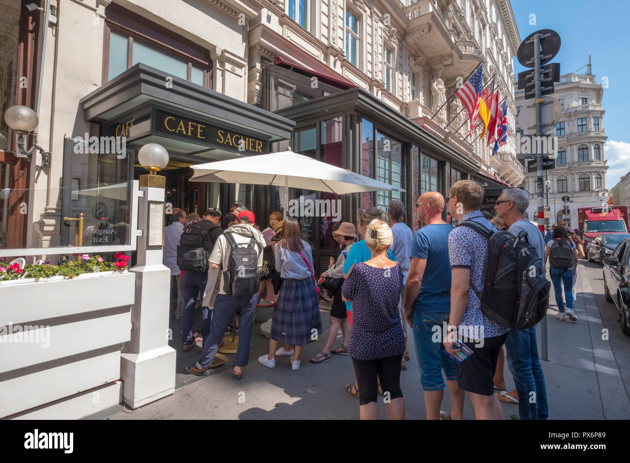 Tourists queue at the entrance of the famous Cafe Sacher in Vienna, Austria, Europe - Stock Image