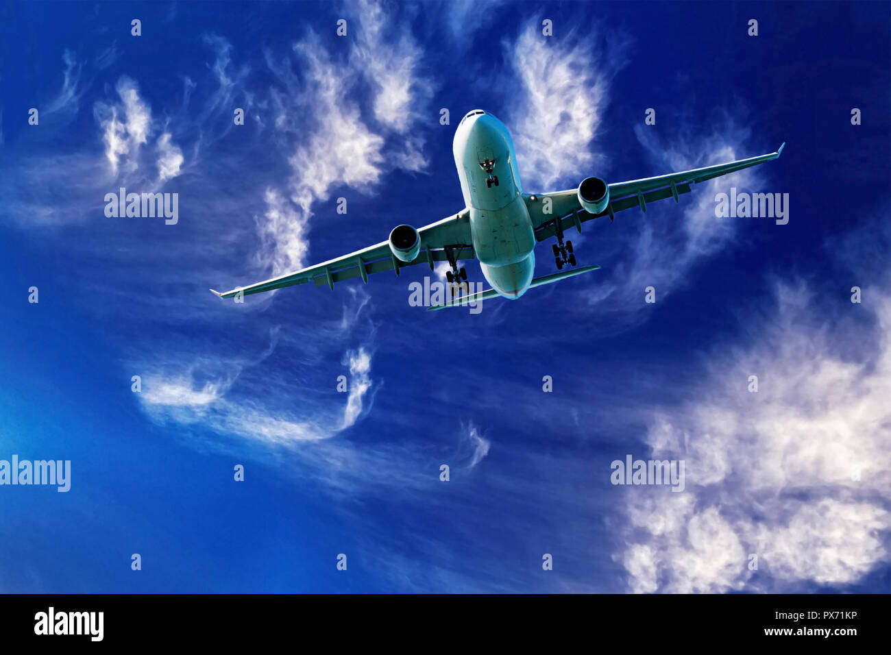 A closeup skyscape view of a commercial passenger jet aircraft flyng in a vibrant blue sky, with bright white coloured wispy cirrus clouds. Australia. - Stock Image