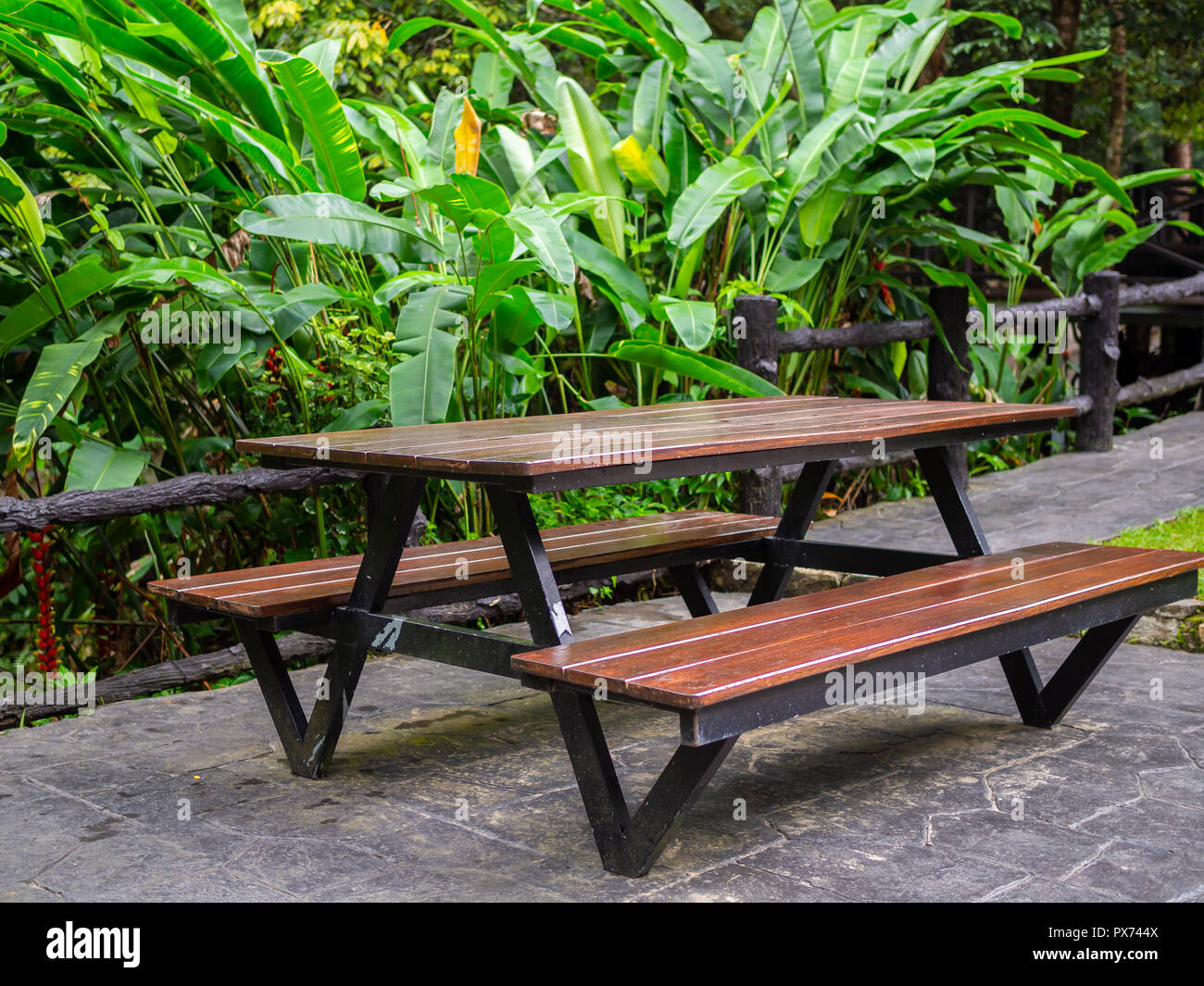 Wooden patio chair reclaimed wood outdoor dining table on tropical rainforest background. & Wooden patio chair reclaimed wood outdoor dining table on tropical ...
