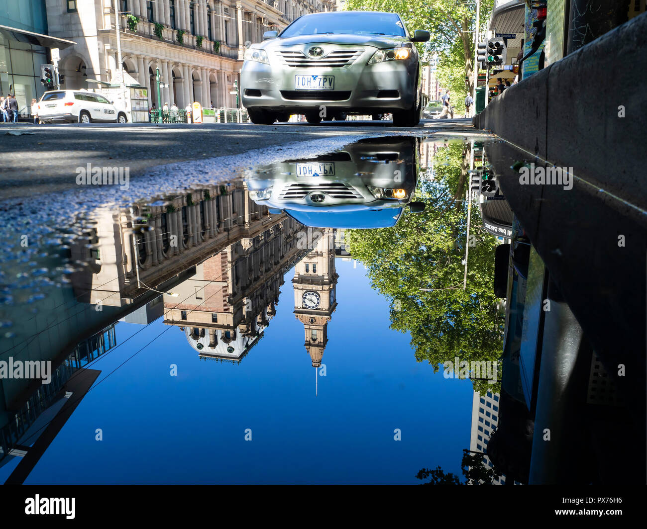 A moment in time caught as reflections of city buildings and multiple people going about their life are seen in a distorted view in a puddle - Stock Image