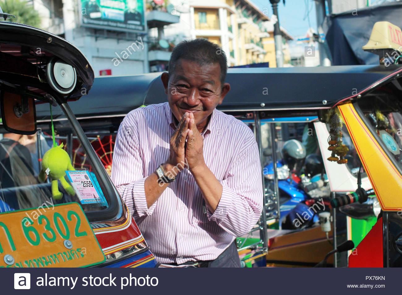 Bangkok, Thailand - 10.30.2015 - portrait of smiling and bowing tuk tuk driver between tuk tuks - Stock Image
