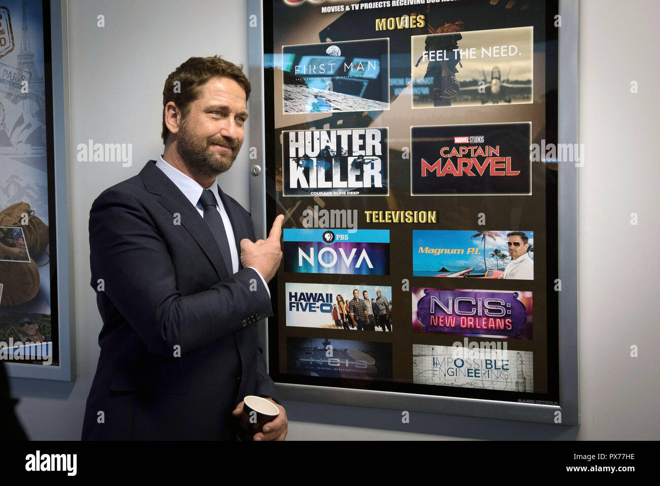 Scottish actor Gerard Butler poses with movie posters from