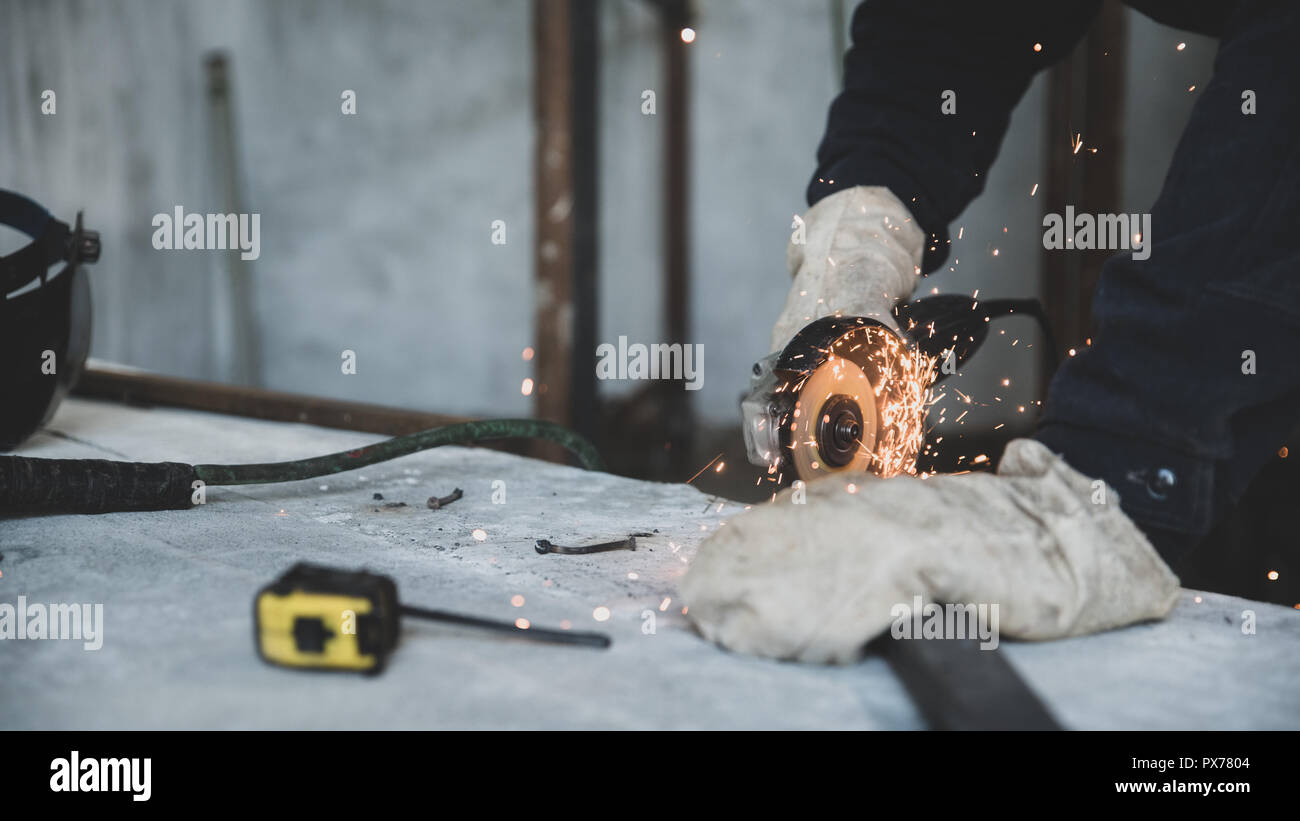 Profession and skill. Process of cutting metal profile with electric angle grinder. Preparation of parts for welding of metal construction. Matte toni - Stock Image