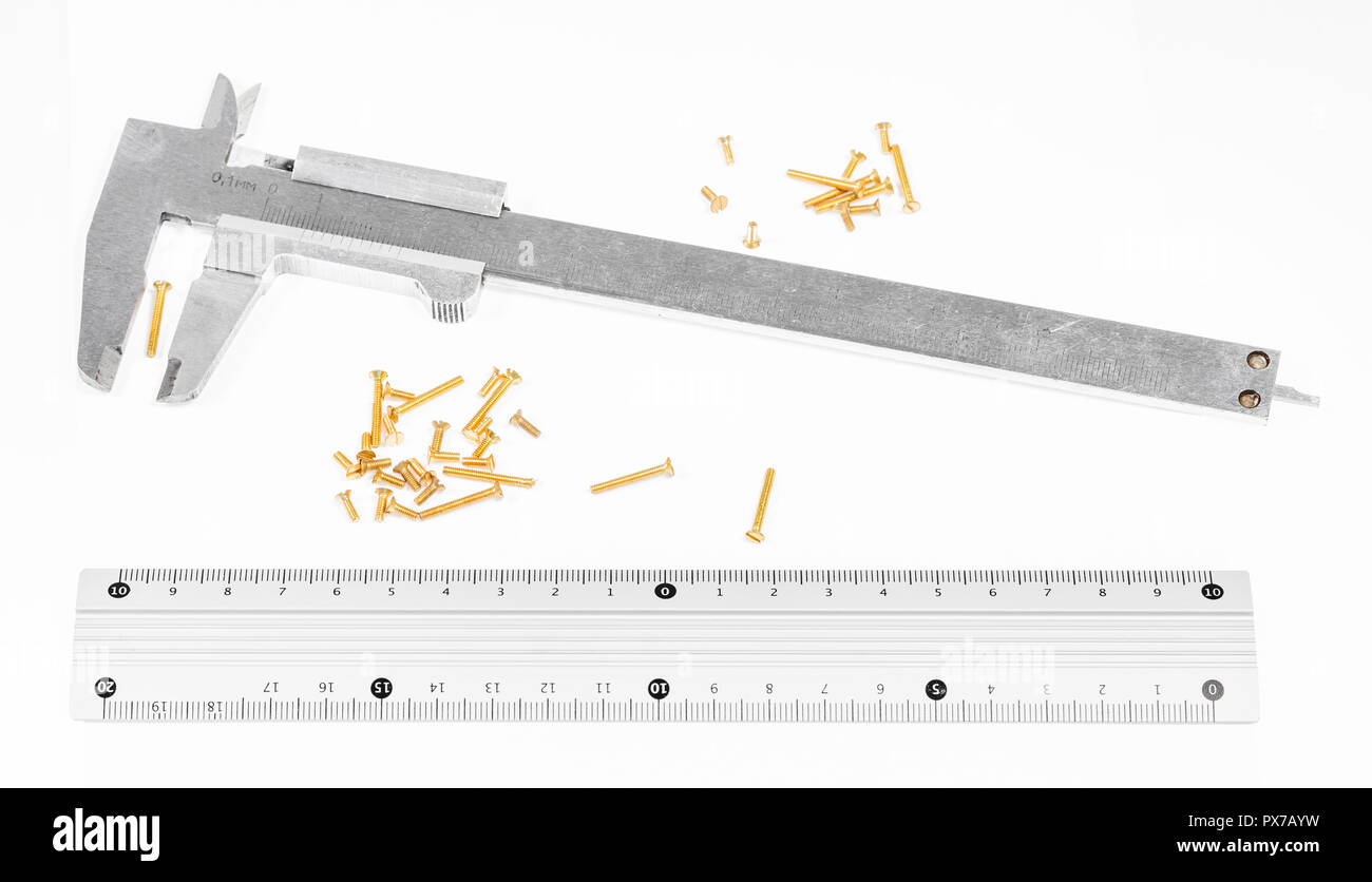 old steel calipers, metallic ruler and many of brass screws on white background - Stock Image