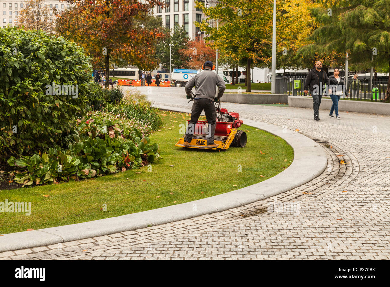 A man on a stand on lawn mower cutting the grass in London,England,UK - Stock Image