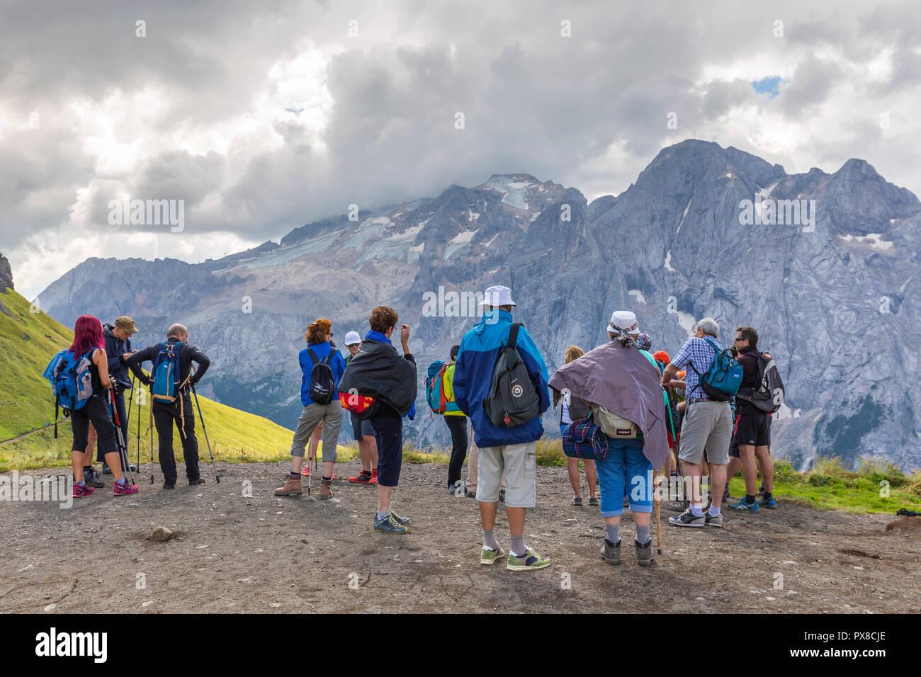 Group of tourist looks Marmolada. Pordoi Pass, Fassa Valley, Trentino, Dolomites, Italy, Europe. - Stock Image
