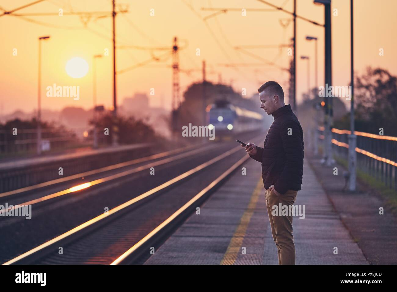 Young man waiting at railroad station platform and using smart phone against commuting train at sunrise. - Stock Image