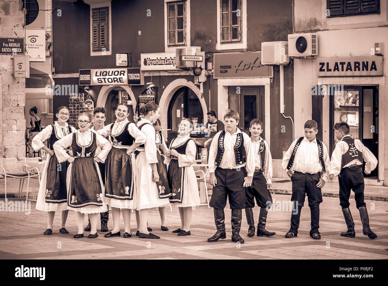 MAKARSKA, CROATIA - JULY 19, 2018: Young artists wearing national costumes prepare for a street performance in Makarska city, Croatia Stock Photo