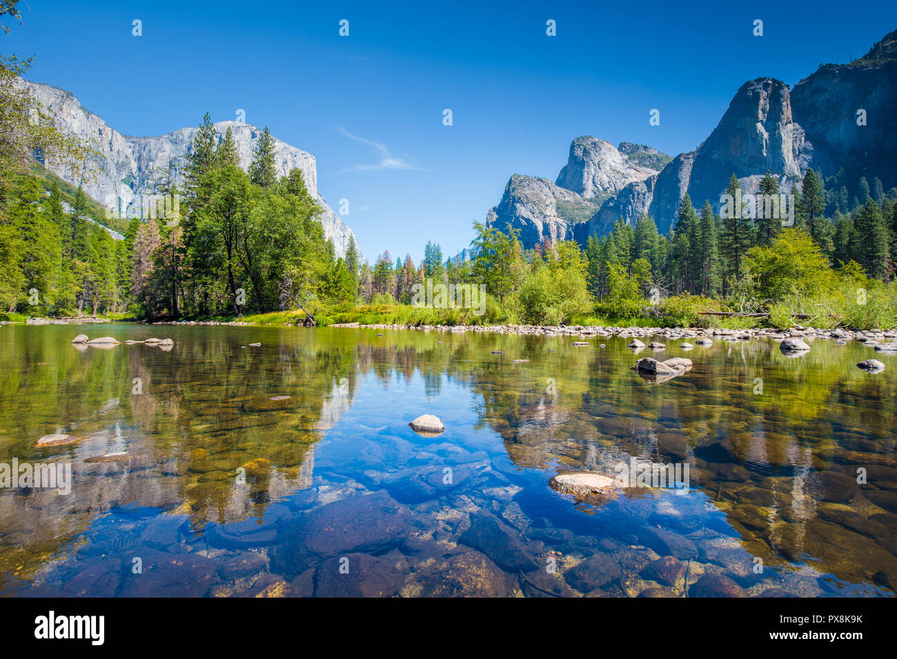 Classic view of scenic Yosemite Valley with famous El Capitan rock climbing summit and idyllic Merced river on a sunny day with blue sky and clouds - Stock Image