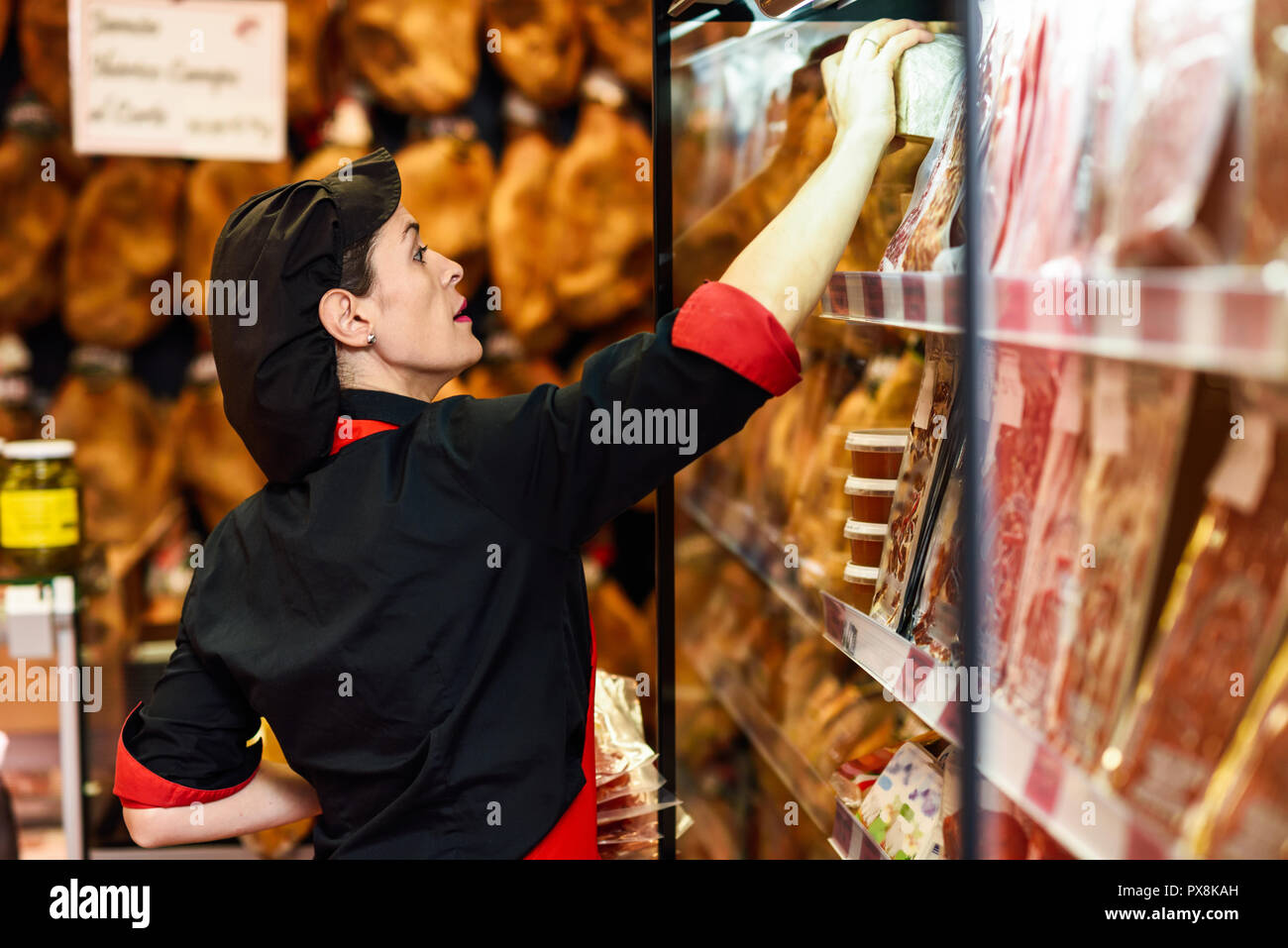 Portrait of female worker taking products in butcher shop. Refrigerated display case for sausage packages, ham and cheese - Stock Image