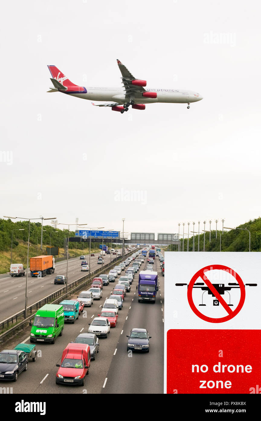 Traffic congestion on the M1 motorway at Loughborough due to sheer volume of traffic, with a plane coming into land at East Midlands Airport with a no Stock Photo