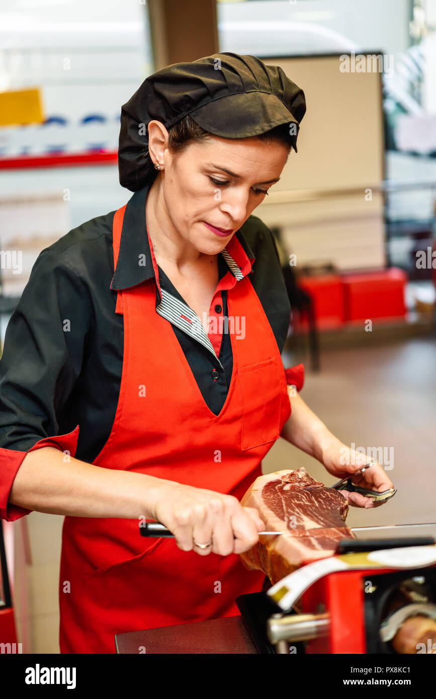Professional female cutter carving slices from a whole bone-in serrano ham - Stock Image