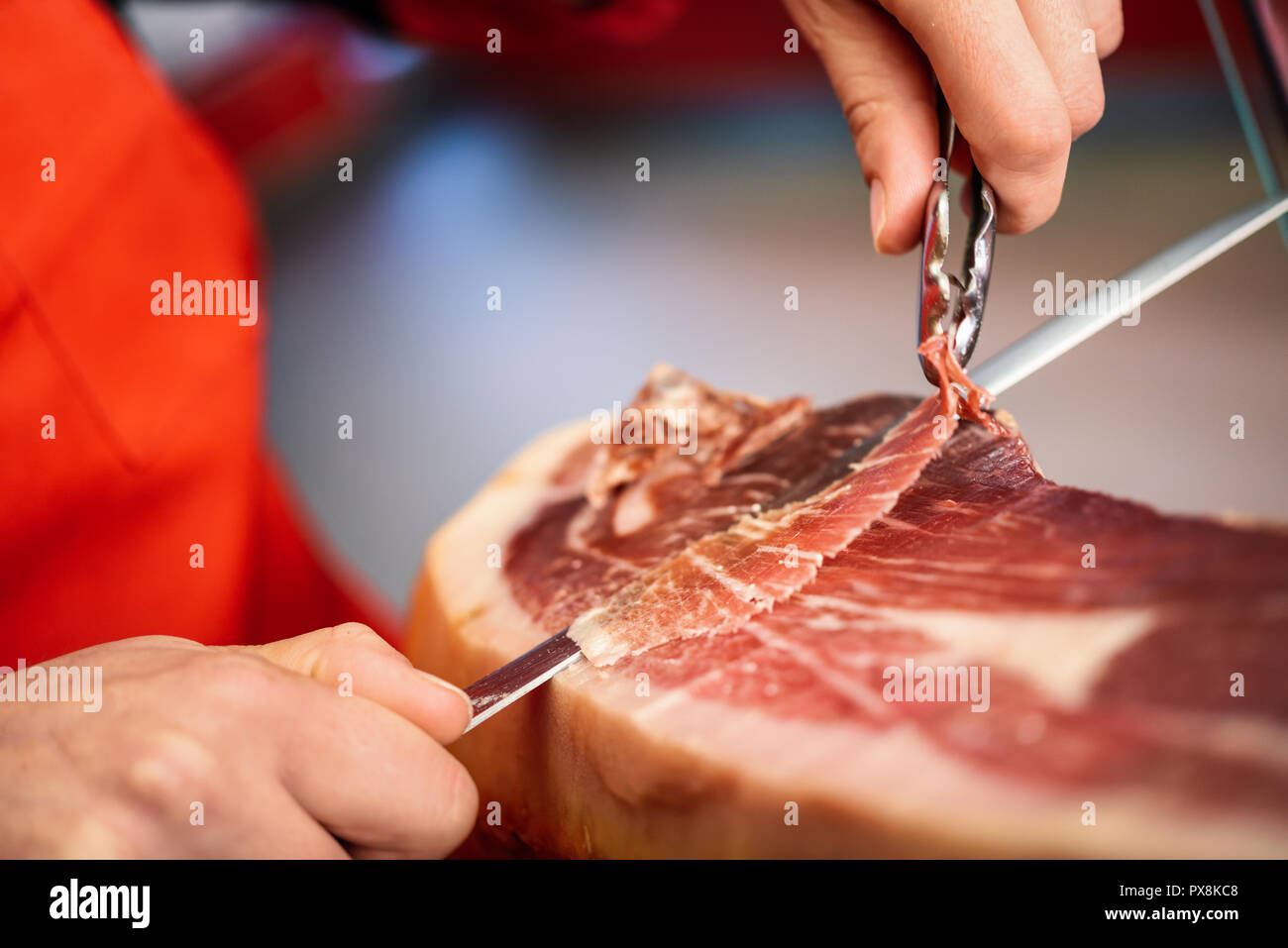 Close-up of professional cutter carving slices from a whole bone-in serrano ham - Stock Image