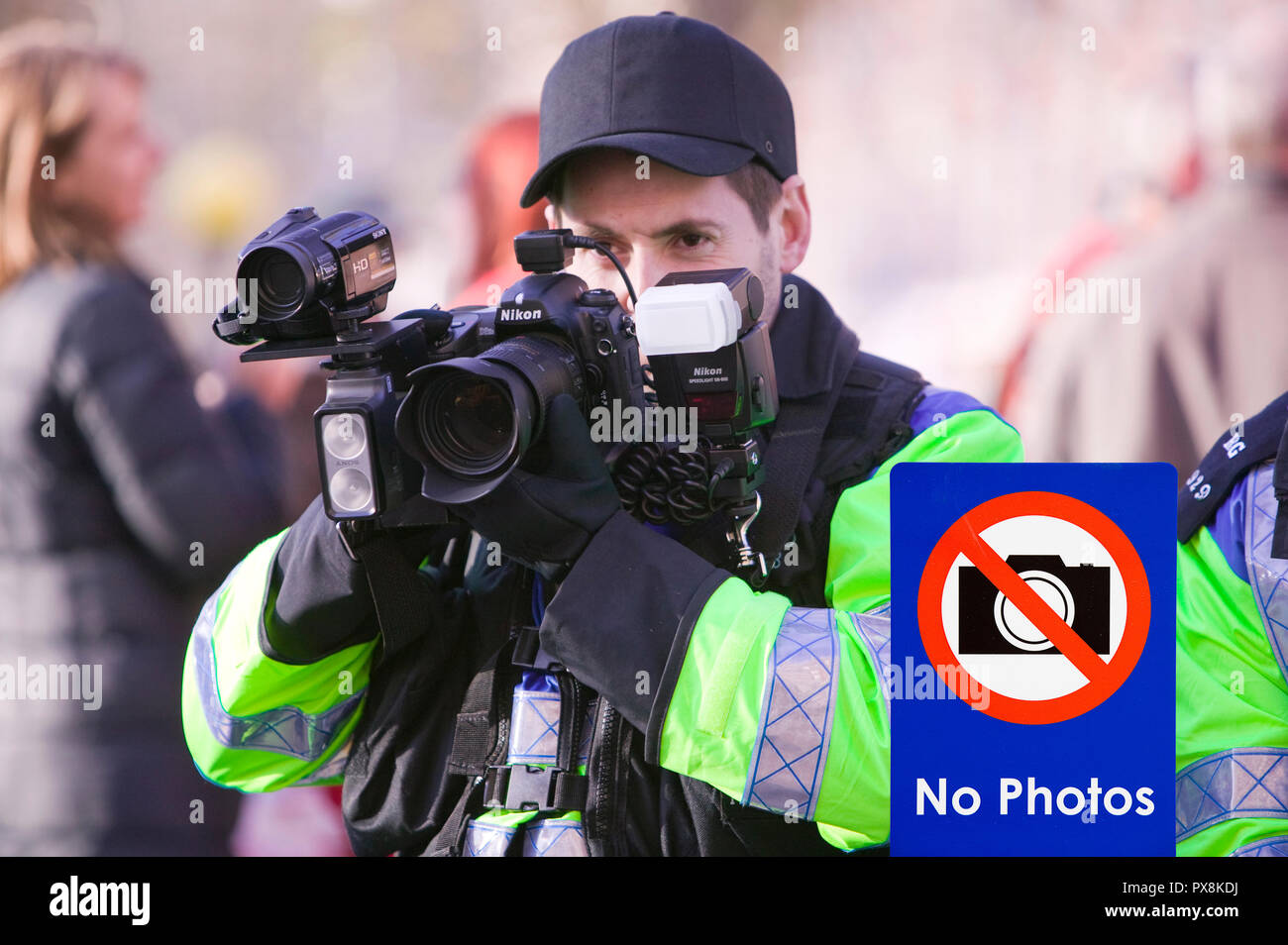 Police photographer photographing protestors at a climate change rally in London December 2008 with a no photos sign. - Stock Image