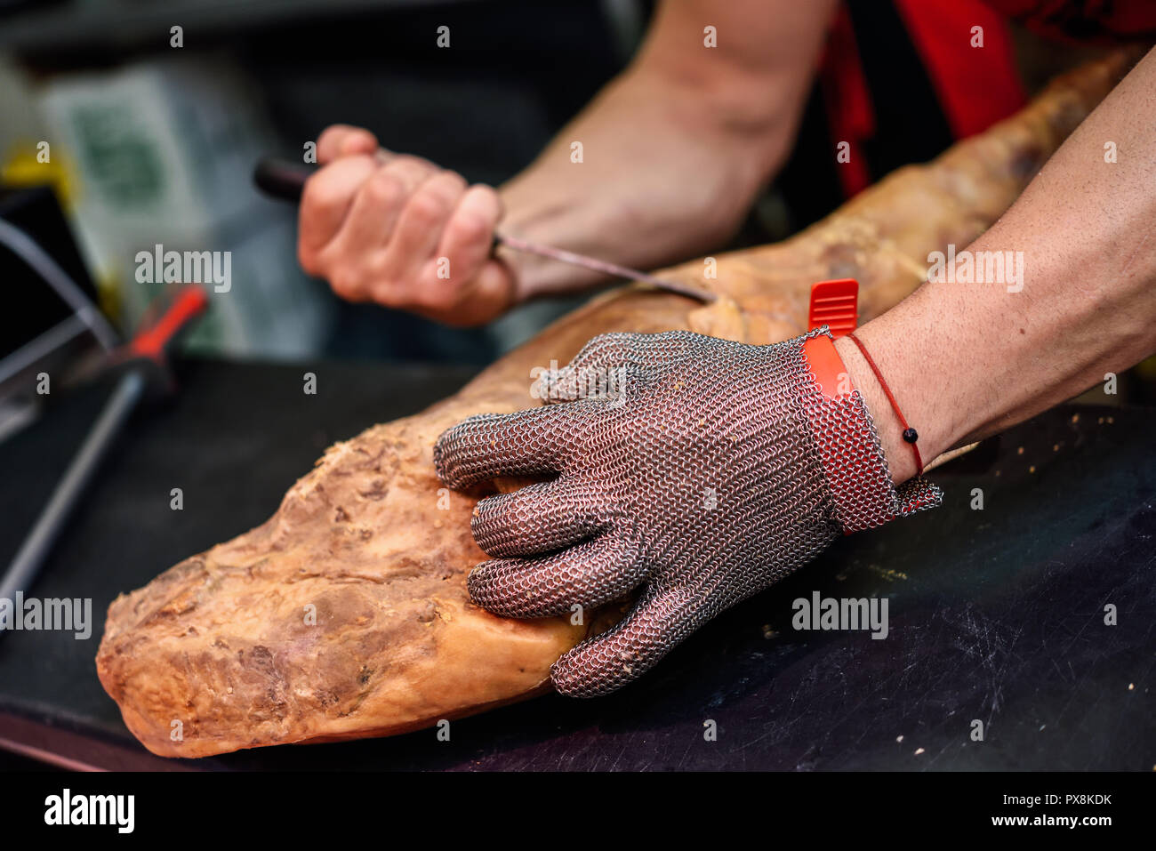 Close-up of butcher boning a ham in a modern butcher shop with metal safety mesh glove - Stock Image