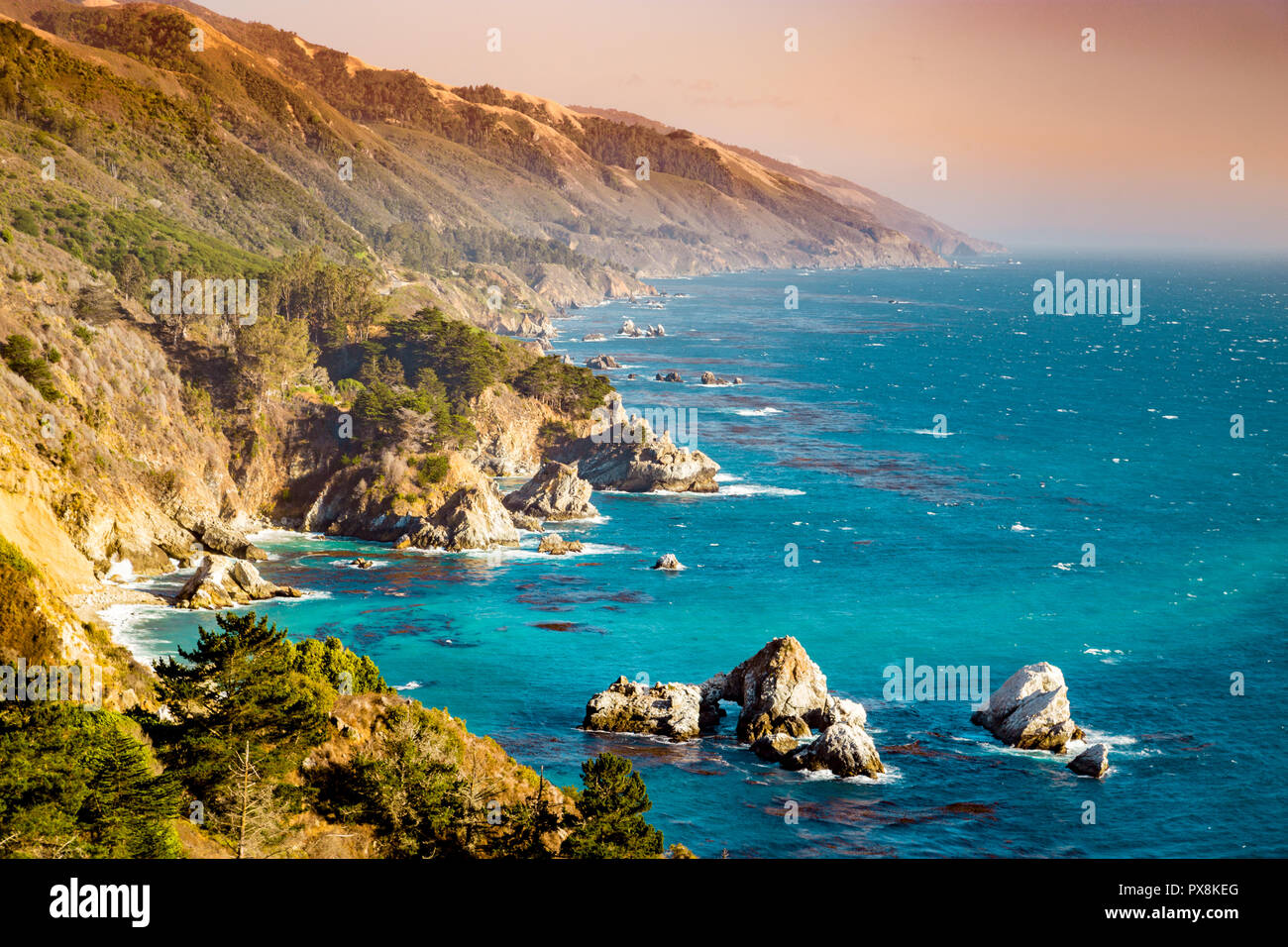 Scenic view of the rugged coastline of Big Sur with Santa Lucia Mountains along famous Highway 1 illuminated in beautiful golden evening light at suns - Stock Image