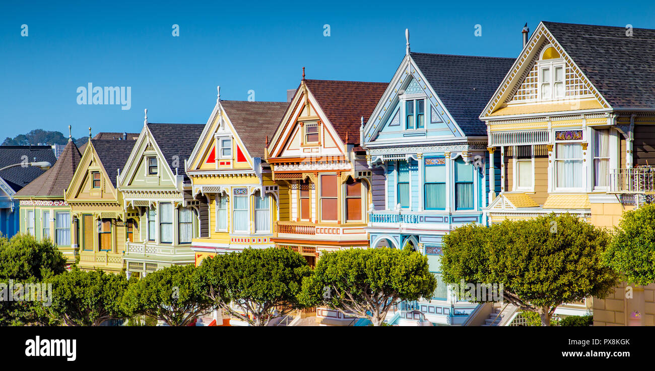 Classic postcard view of famous Painted Ladies, a row of colorful Victorian houses located near scenic Alamo Square, on a beautiful sunny day with blu - Stock Image