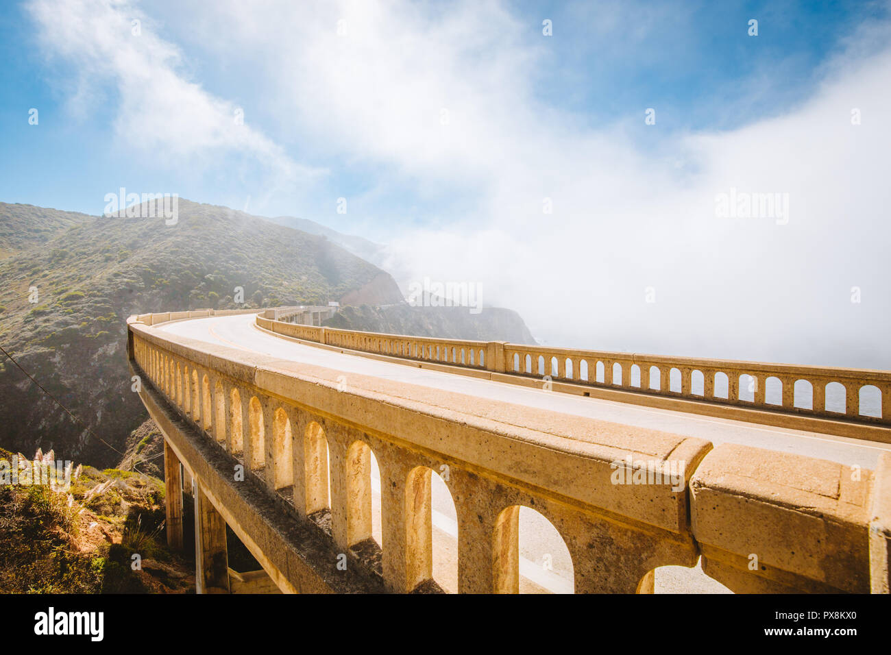 Panoramic view of historic Bixby Creek Bridge along world famous Highway 1 on a sunny day with fog in summer, Monterey County, California, USA Stock Photo