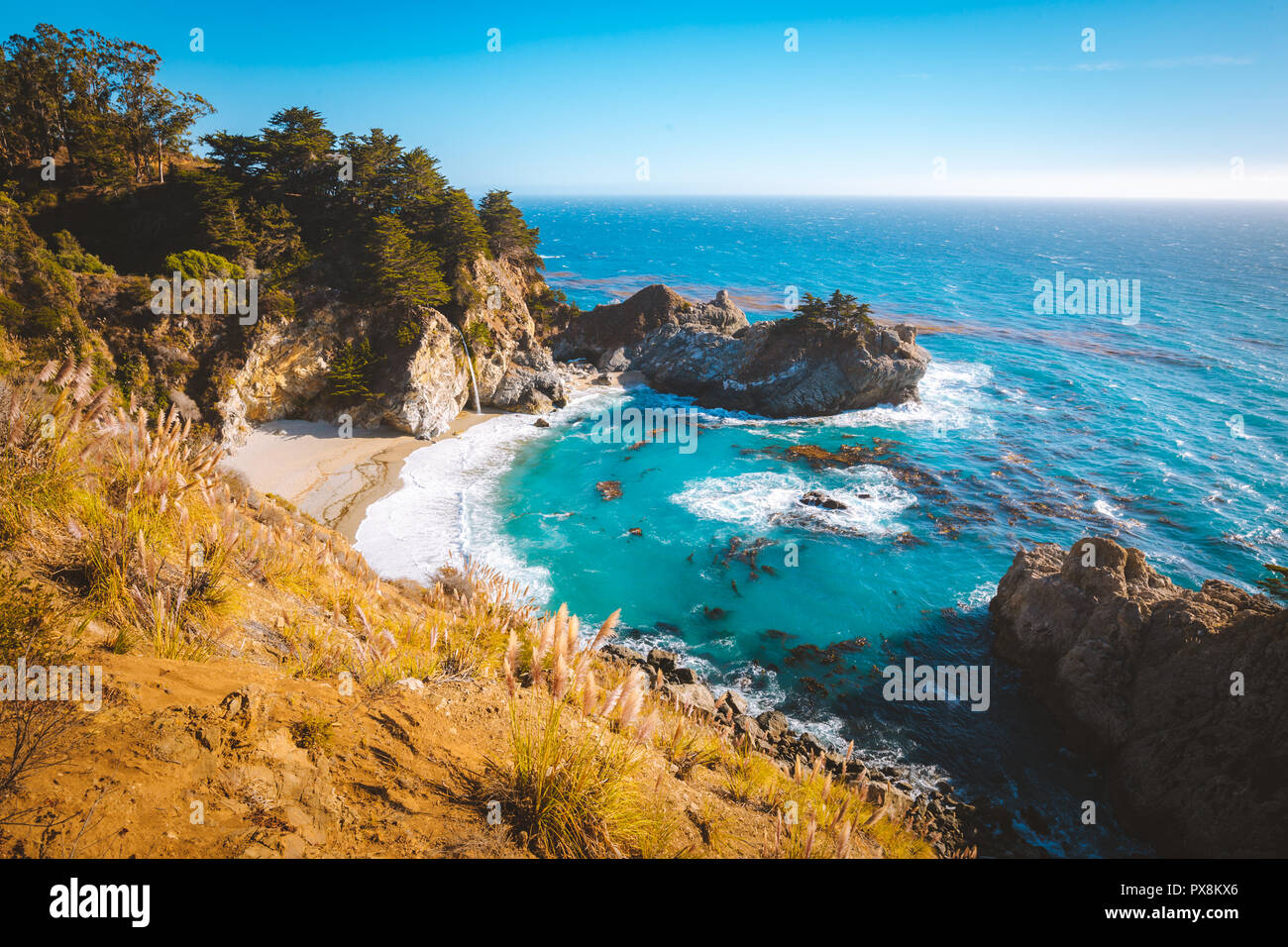 Classic postcard view of famous McWay Falls in scenic golden evening light at sunset on a beautiful sunny day with blue sky in summer, California, USA - Stock Image
