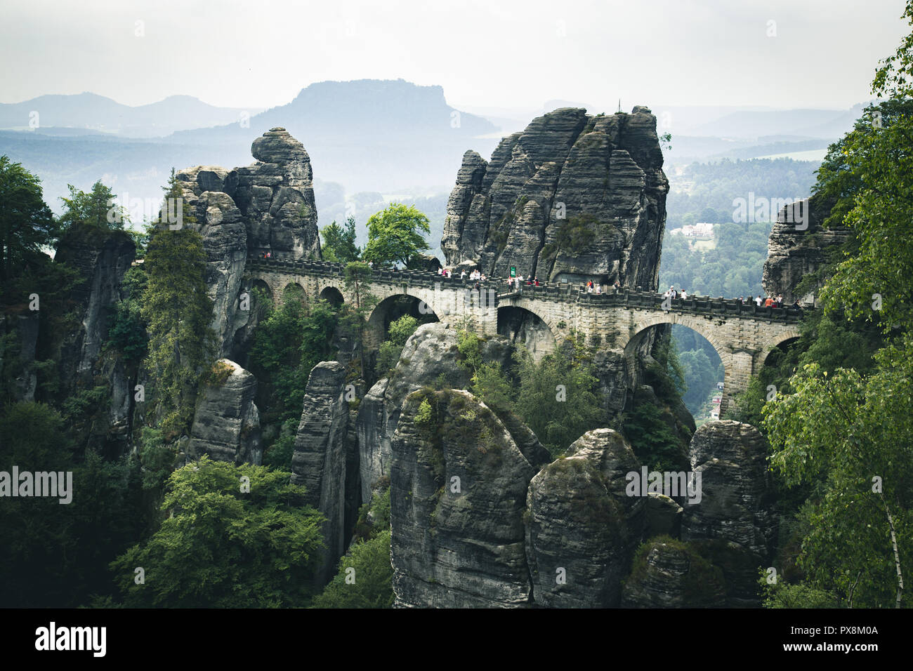 Beautiful panoramic view of famous Bastei Bridge with Elbe Sandstone mountains in Saxon Switzerland National Park on a moody day, Saxony, Germany - Stock Image
