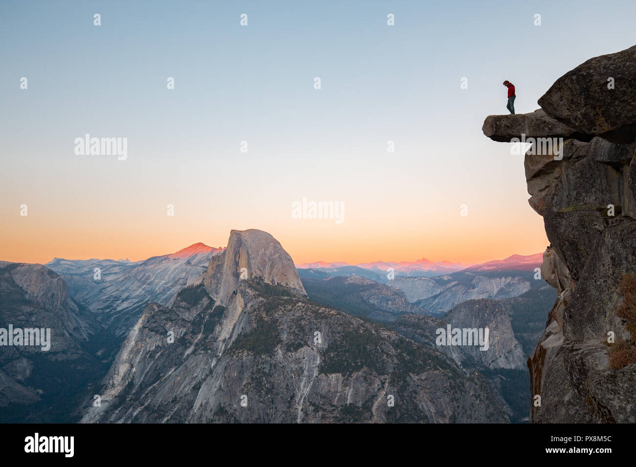 A fearless hiker is standing on an overhanging rock enjoying the view towards famous Half Dome at Glacier Point overlook in beautiful evening twilight - Stock Image