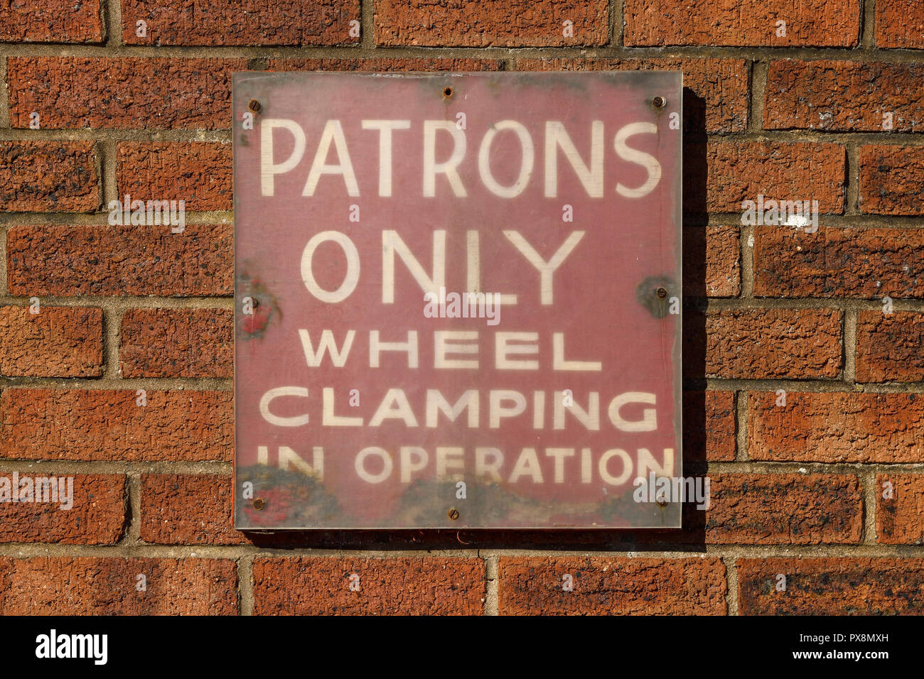 Patrons only wheel clamping in operation sign on a brick wall - Stock Image