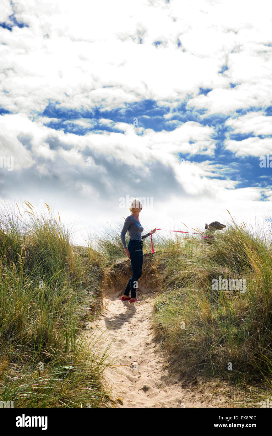 Walking with dog in the sand dunes at Thornham, Norfolk, England - Stock Image