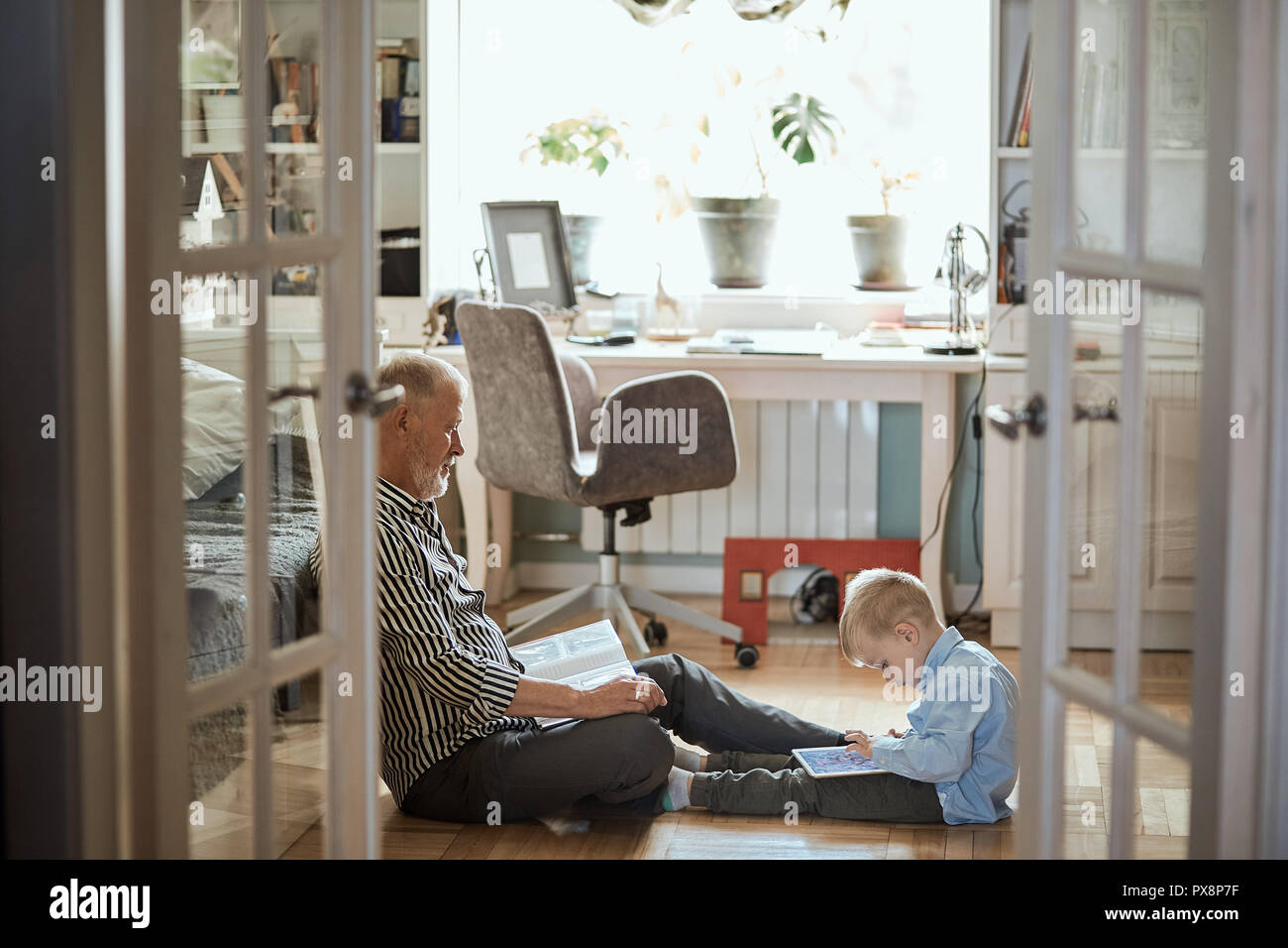 Grandpa looks photo album with his wedding, little boy using electronic tablet - Stock Image