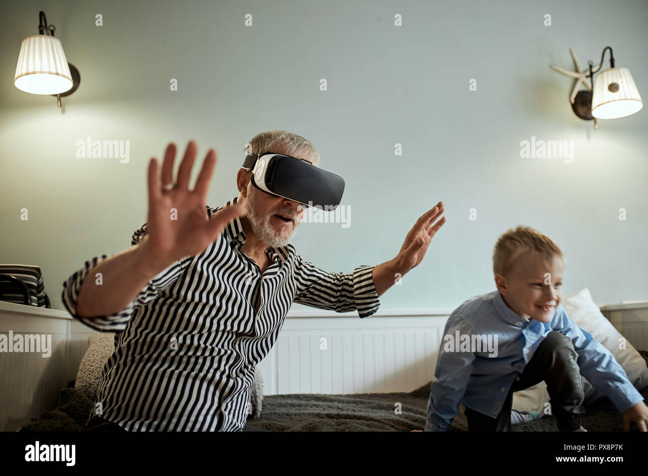 boy and his grandpa using vr glasses on sofa at home - Stock Image