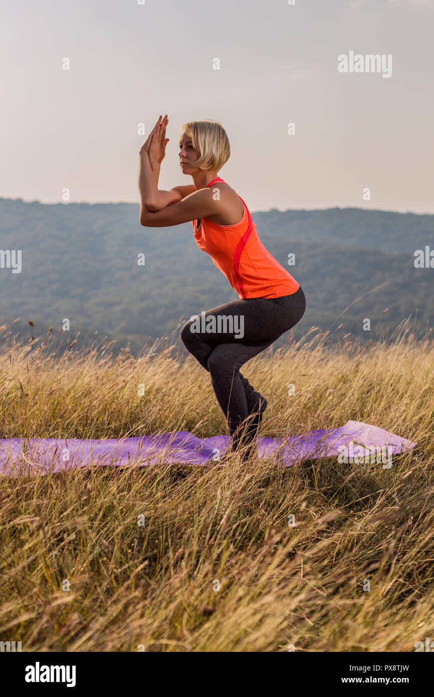 Beautiful woman doing yoga in the nature,Garudasana/Eagle Pose. - Stock Image