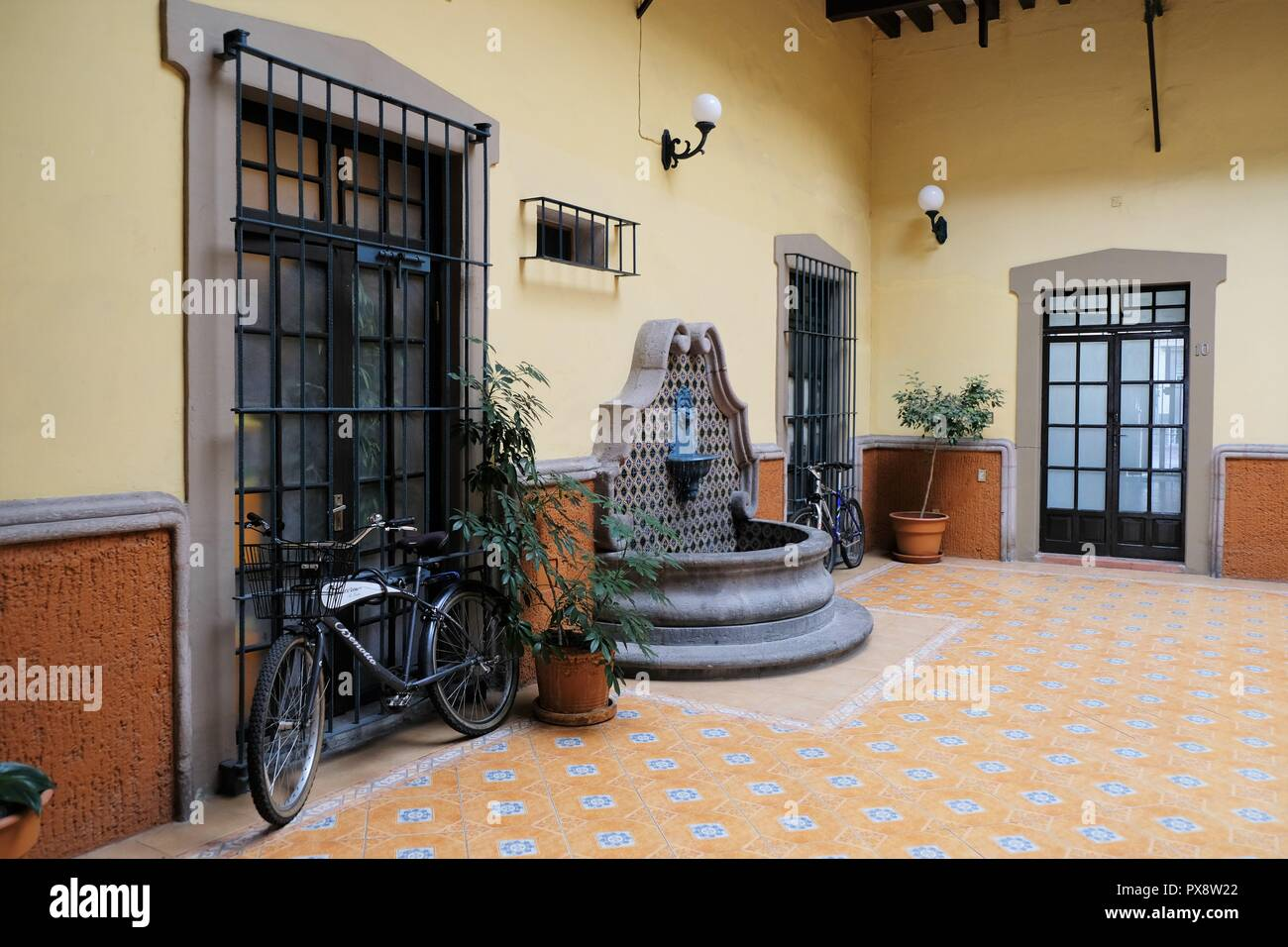 Interior of a courtyard in a traditional colonial era home in the city of queretaro queretaro mexico fountain bicycle window with bars