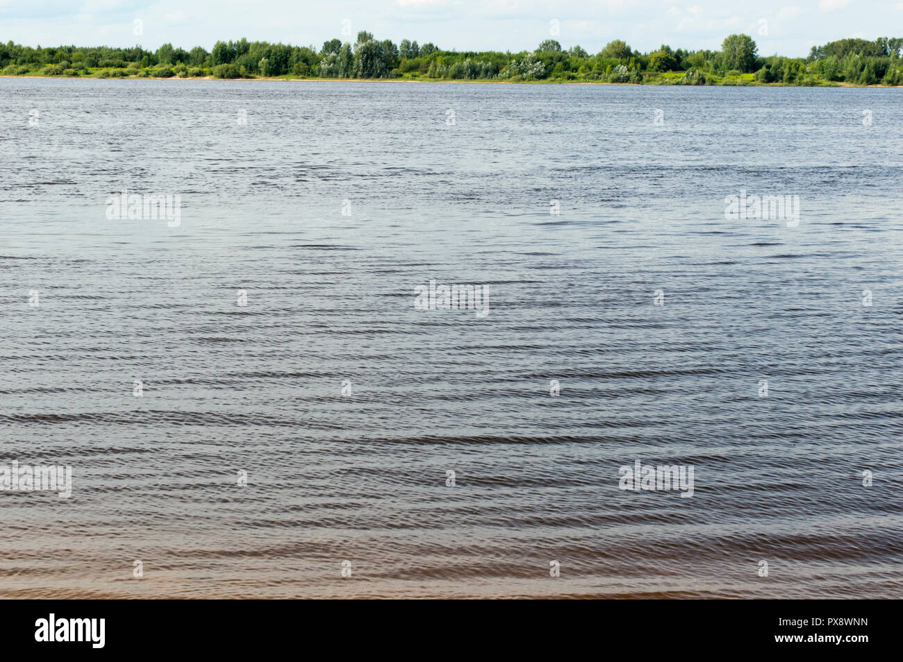 The creek flows into the Volga. Current water and rocks on the bottom. - Stock Image