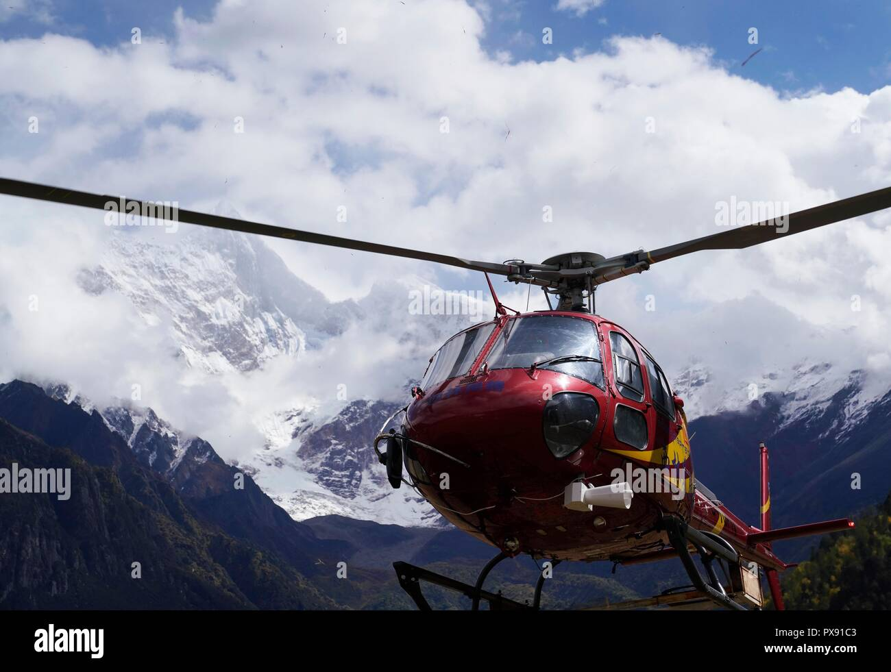 Menling, China's Tibet Autonomous Region. 20th Oct, 2018. A helicopter carries relief materials for the lanslide-caused barrier lake disaster area in Menling County, southwest China's Tibet Autonomous Region, on Oct. 20, 2018. A helicopter from Xilin Fengteng General Aviation Co., Ltd. took part in the disaster relief to transport relief materials. The barrier lake was formed near a village in Menling County after landslides on Wednesday and Thursday blocked the Yarlung Tsangpo River's waterway. Credit: Purbu Zhaxi/Xinhua/Alamy Live News - Stock Image
