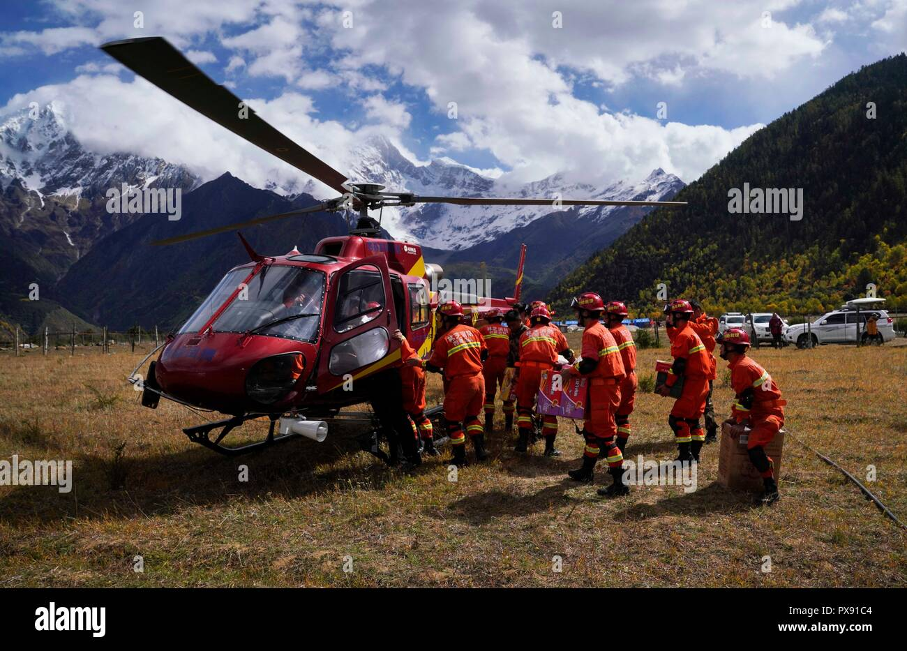 Menling, China's Tibet Autonomous Region. 20th Oct, 2018. Rescuers load a helicopter with relief materials for the lanslide-caused barrier lake disaster area in Menling County, southwest China's Tibet Autonomous Region, on Oct. 20, 2018. A helicopter from Xilin Fengteng General Aviation Co., Ltd. took part in the disaster relief to transport relief materials. The barrier lake was formed near a village in Menling County after landslides on Wednesday and Thursday blocked the Yarlung Tsangpo River's waterway. Credit: Purbu Zhaxi/Xinhua/Alamy Live News - Stock Image