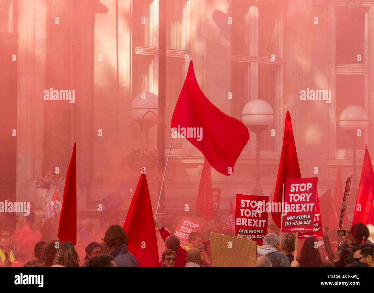 """UK. 20th Oct, 2018. Red flags and placards saying """"Stop Tory Brexit"""" are waved against a backdrop of red smoke from flares let off during the People's Vote March against Brexit on 20th October 2018. Organisers claim over 500,000 participants took part in the event. They were campaigning for a referendum of the final terms of the United Kingdom's withdrawal from the European Union Credit: Stephen Taylor/Alamy Live News Stock Photo"""