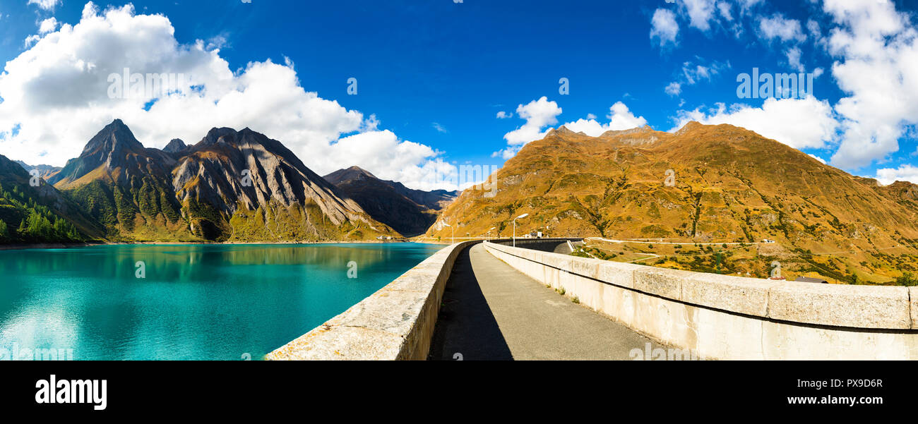 great landscape seen from dam of Morasco Lake with mountains and blue sky in background in a autumn day, Formazza valley - Piedmont, Italy, Europe - Stock Image