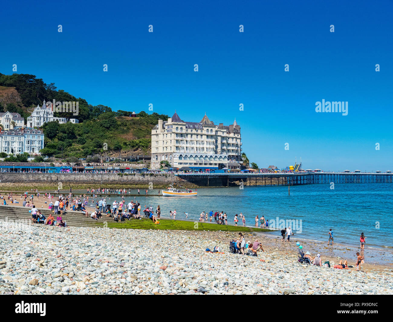 26 July 2018: Llandudno, Conwy, UK - Llandudno beach on a hot summer day, and the Grand Hotel. In the foreground is the pebble sea defence. - Stock Image