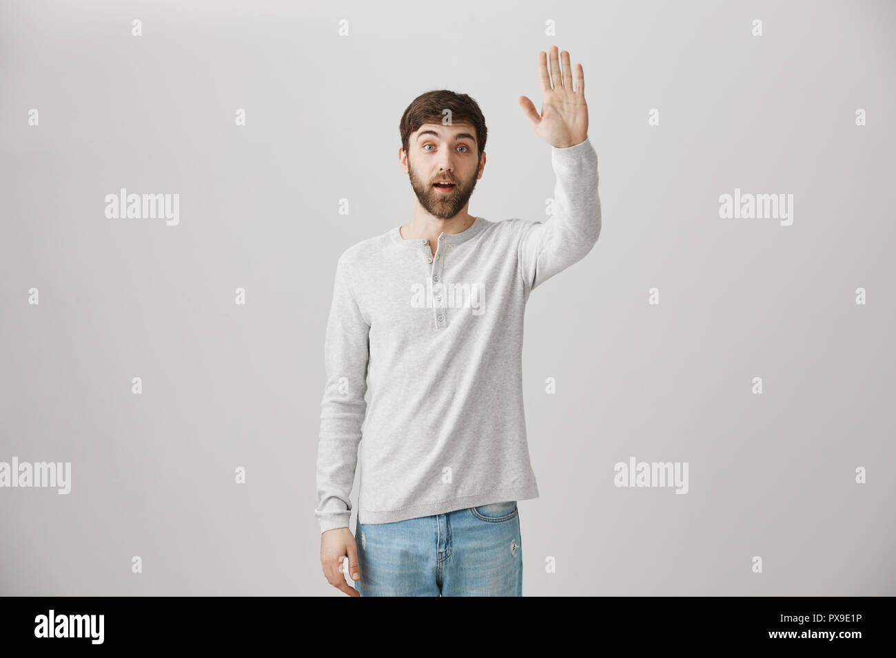 a15e30997 Surprised ordinary bearded guy standing with lifted hand as if waving or  greeting someone on street