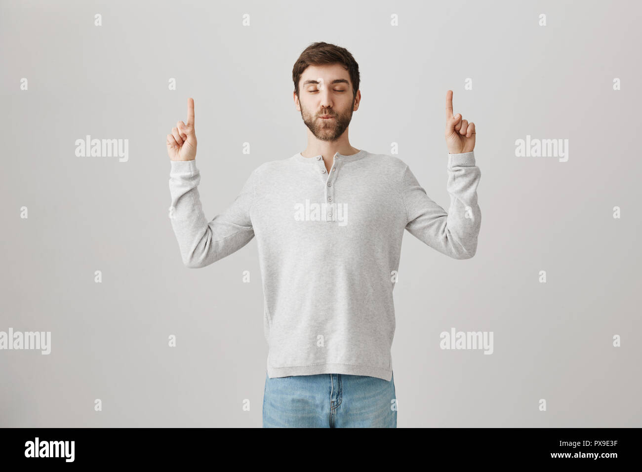 Attractive confident male with beard standing with closed eyes and sucked in lips, feeling narcissistic and calm, pointing up with index fingers. Guy is not surprised he won. Advertisement concept - Stock Image