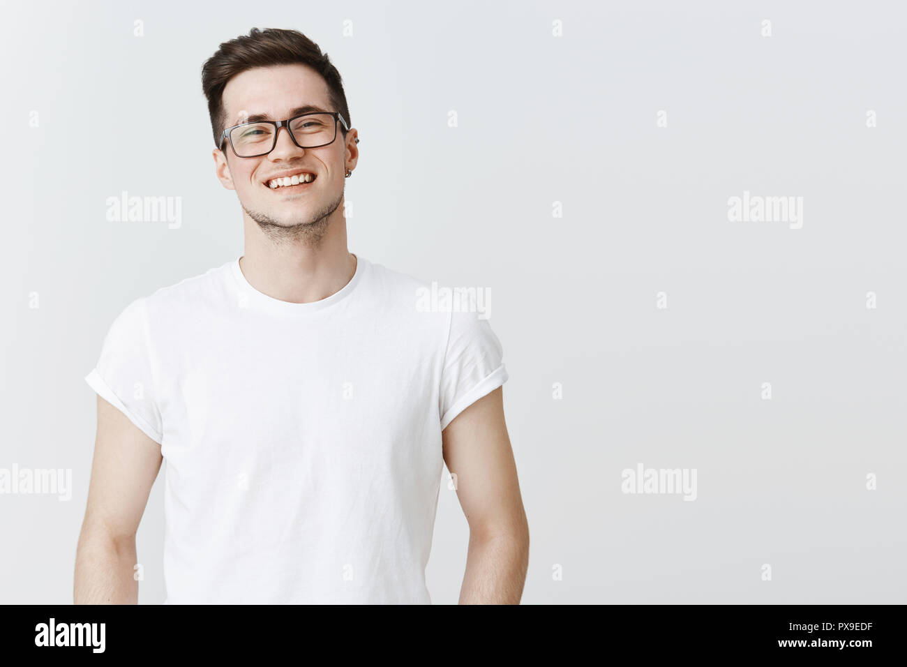 Waist-up shot of pleasant and friendly-looking handsome happy young guy in glasses smiling broadly as standing over gray copy space carefree and joyful living fulfilled life, enjoying conversation - Stock Image