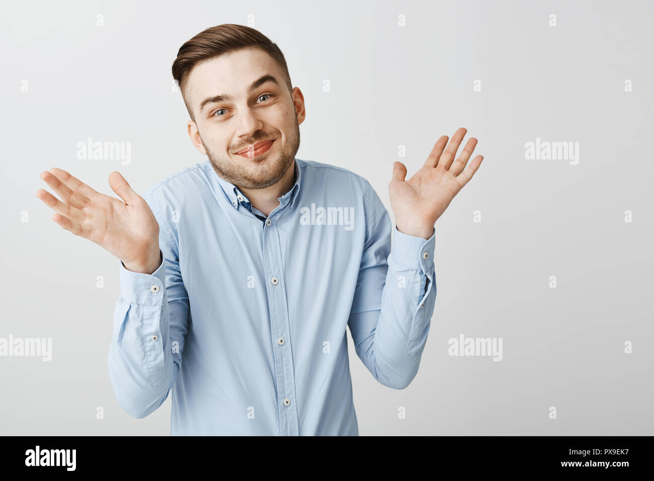 No idea guess yourself. Portrait of happy carefree and careless good-looking male coworker in blue shirt shrugging with raised palms tilting head and smiling with sorry look being unaware and clueless Stock Photo