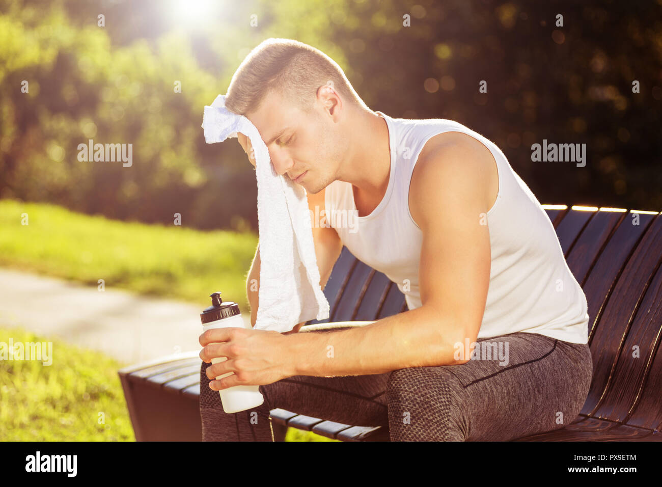 Exhausted man after exercise drinking water and wiping sweat with towel. - Stock Image