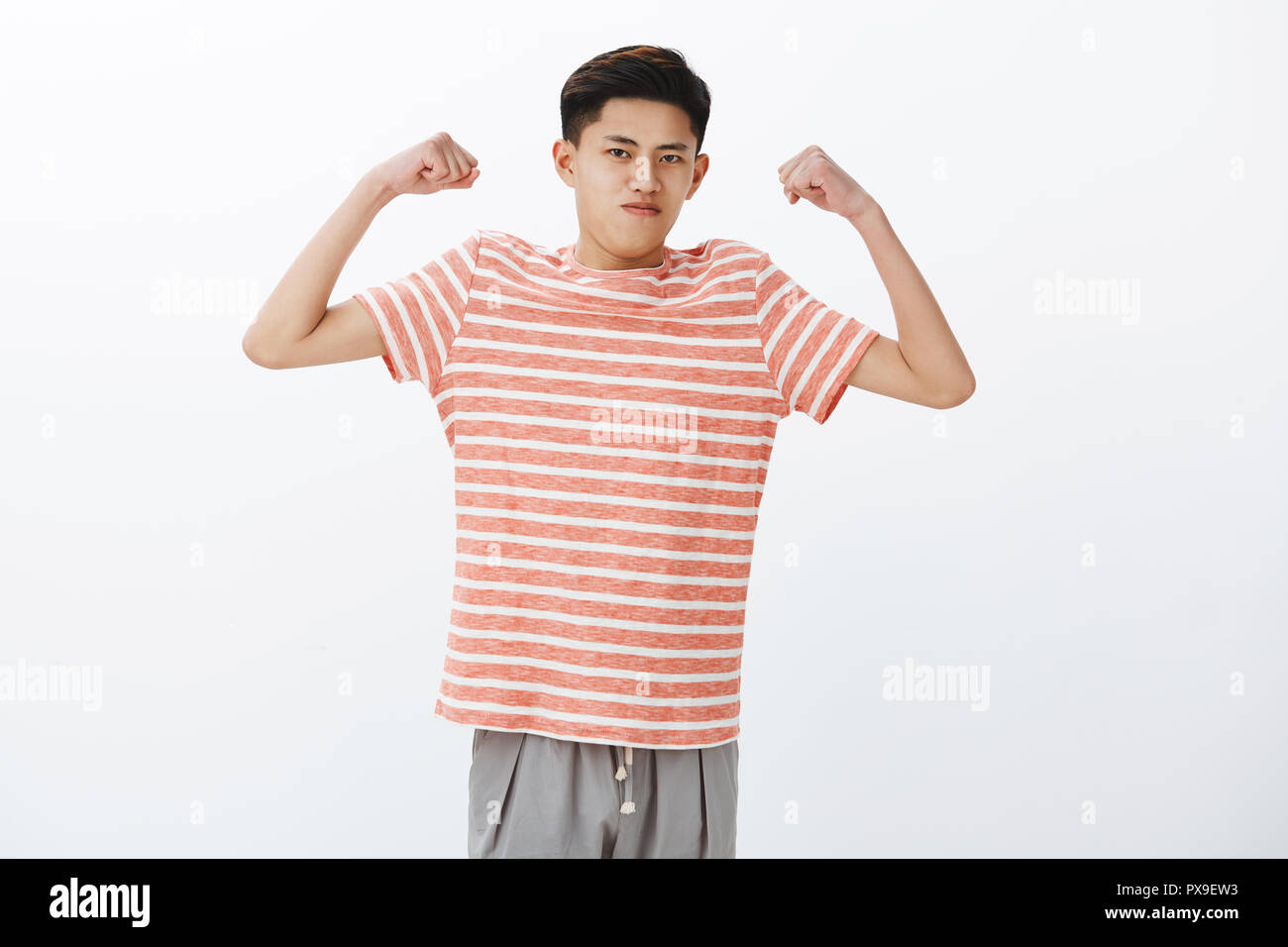 Look how strong I am. Portrait of self-assured funny young slim asian guy raising hands to show biceps or muscles, starting working out, straining and holding breath to look masculine - Stock Image