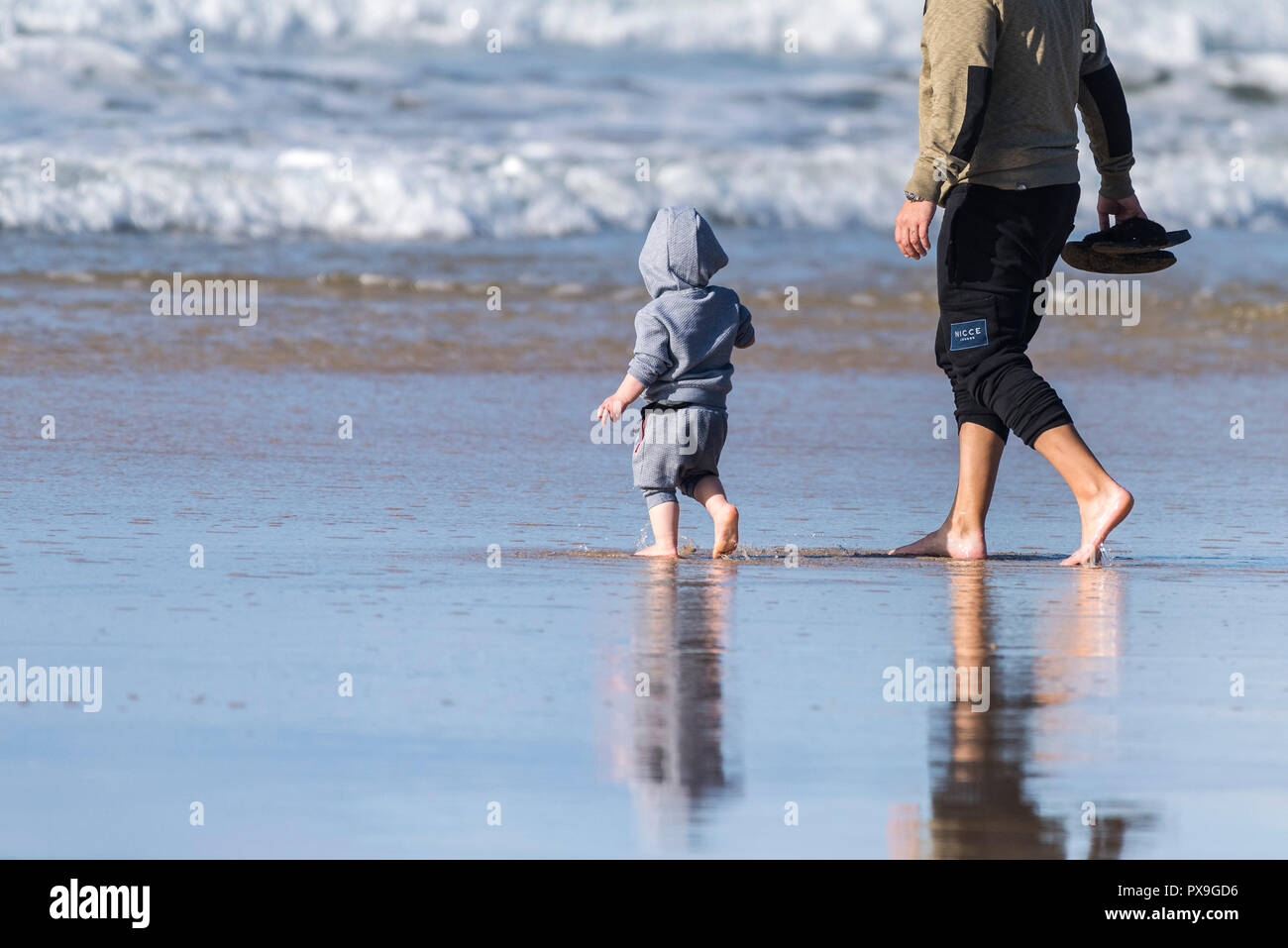 A father and his young son paddling in the sea at Fistral Beach in Newquay in Cornwall. - Stock Image