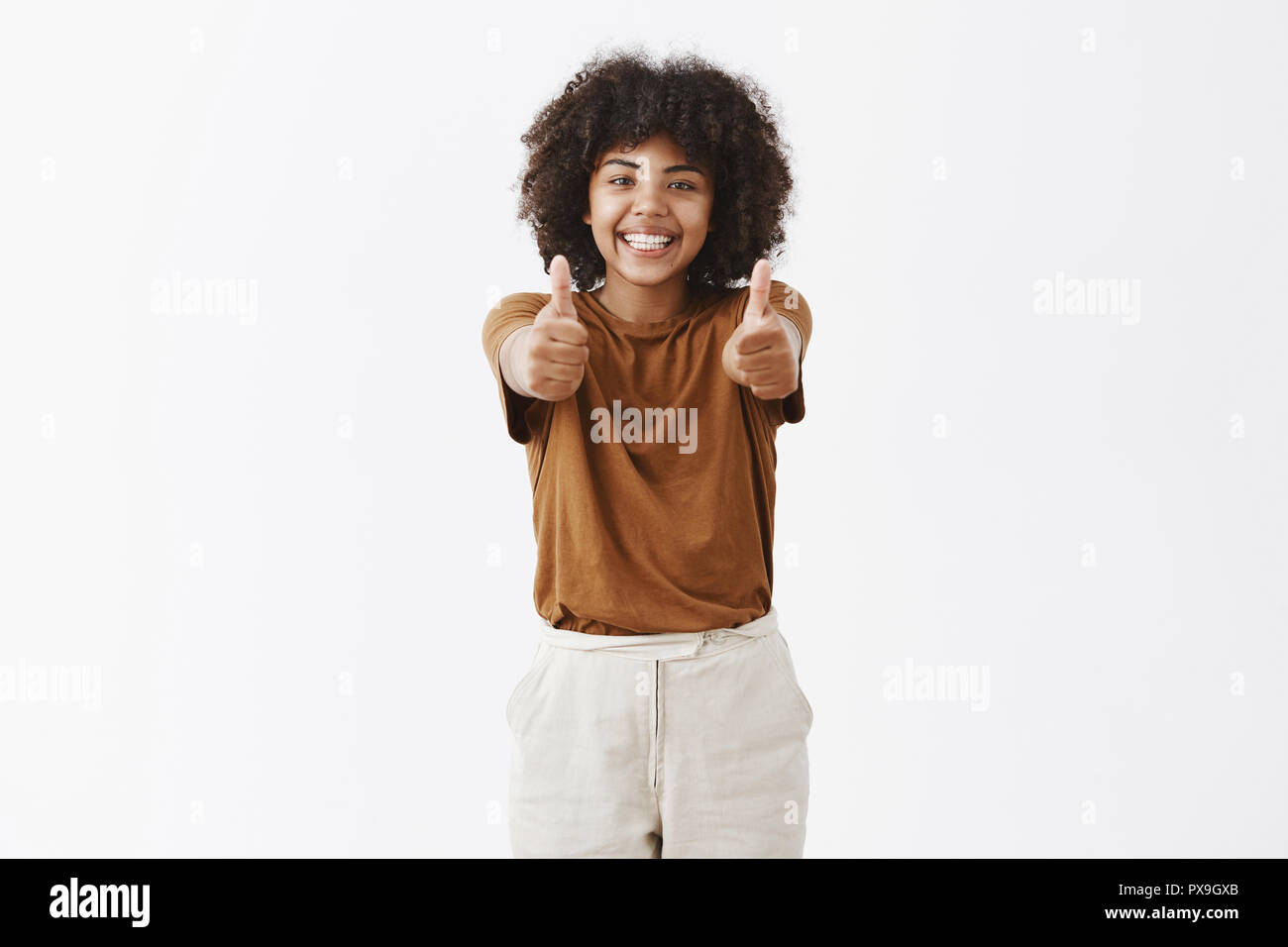 Saying yes to new opportunities. Bright and joyful african american girl with afro hairstyle in stylish brown t-shirt pulling hands towards camera with thumbs up and smiling cheering and supportive - Stock Image