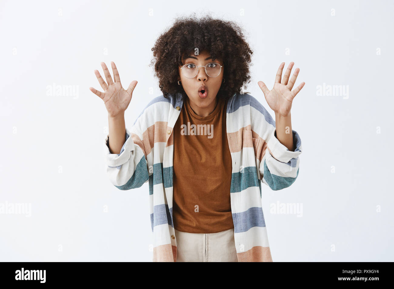 Stay were you are. Excited sociable and creative female with afro hairstyle raising palms and folding lips telling scary story while on trip with friends sitting by fire being persuasive and emotive - Stock Image